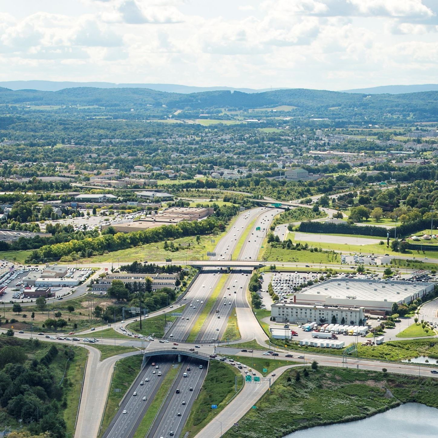 Aerial view of busy interstate and buildings with rolling hills in the distance