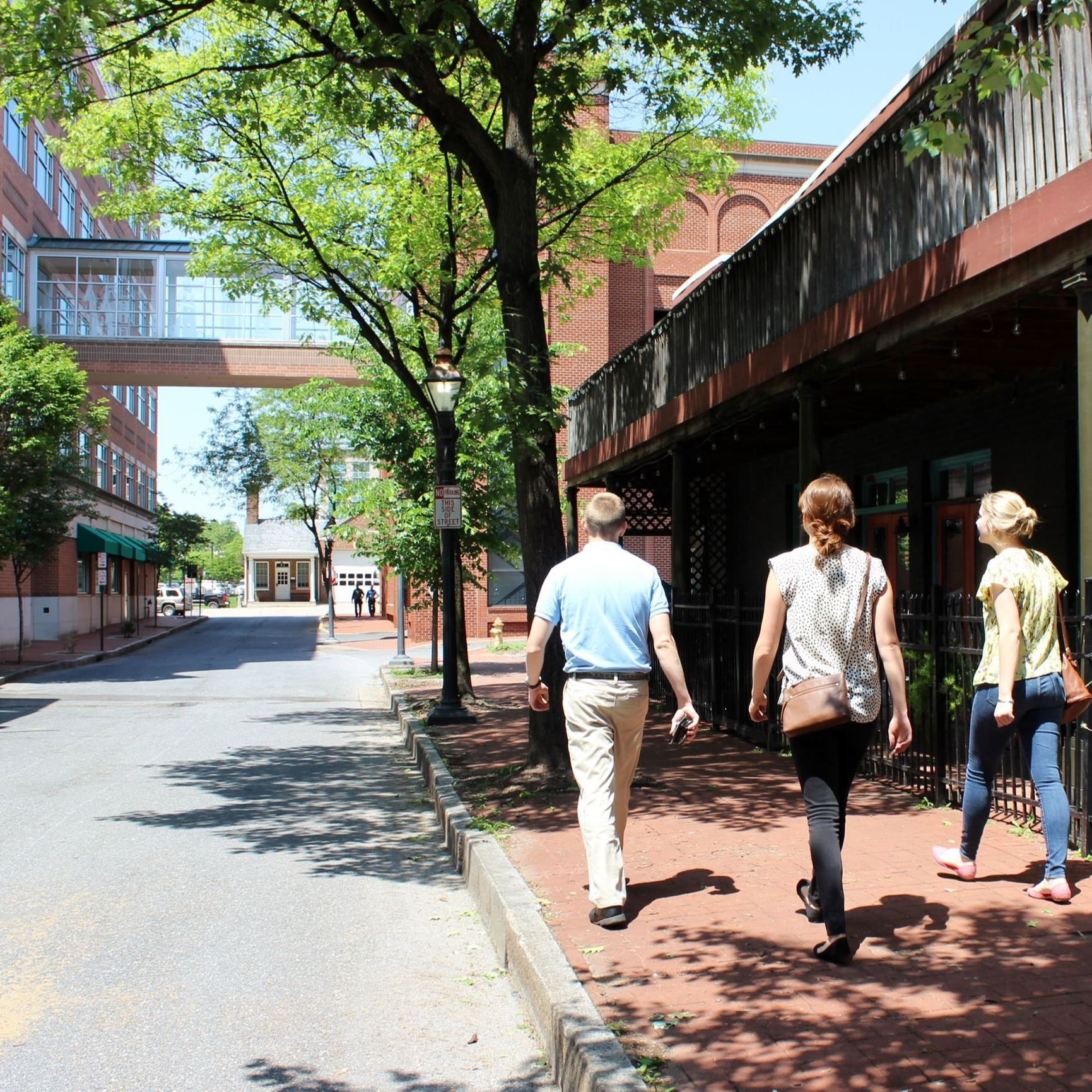 People walking down a street flanked by brick buildings