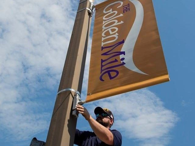Man installing a Golden Mile sign on a light pole